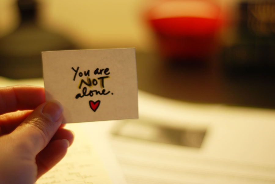 A hand holds up a note that reads 'You are not alone.' with a small heart.