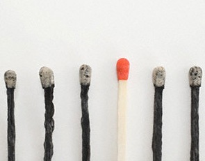 An unlit and burnt matches in a row